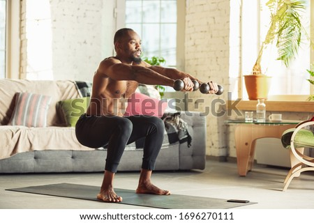 African-american man teaching at home online courses of fitness, aerobic, sporty lifestyle while being quarantine. Getting active while isolated, wellness, movement concept. Training with weights. #1696270111