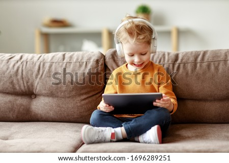 Full body delighted little boy in headphones smiling and watching interesting cartoon on tablet while sitting crossed legged on sofa at home