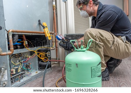 HVAC contractor wearing PPE, servicing a heat pump Royalty-Free Stock Photo #1696328266