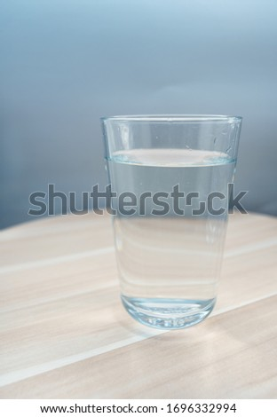 Glass cup with mineral water on a wooden tray. Close-up #1696332994