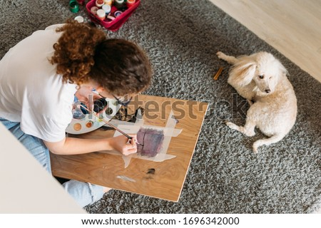 Curly hair smiling girl teenager in glasses in white t-shirt sitting on floor and painting on wooden desk with poodle dog at home