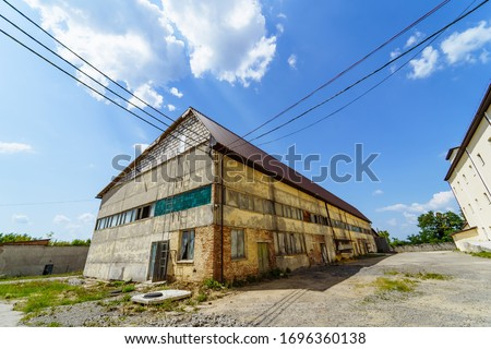 Abandoned factory house. Old industrial building outdoor view on sunny summer day. #1696360138