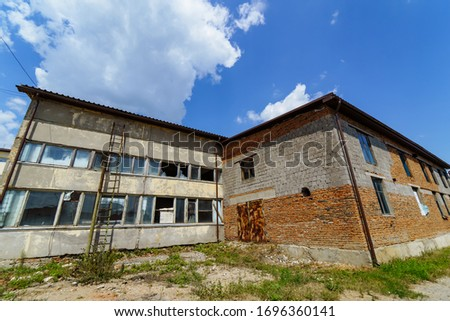 An old abandoned stone building with broken windows. Old warehouse, storehouse, factory. #1696360141