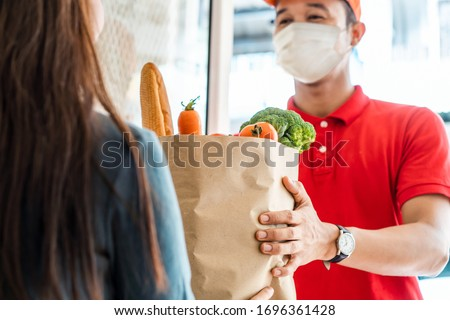 Asian deliver man wearing face mask in red uniform handling bag of food, fruit, vegetable give to female costumer in front of the house. Postman and express grocery delivery service during covid19. #1696361428