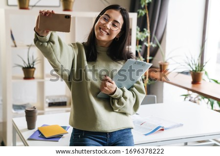 Image of a pretty cute cheerful positive young girl student indoors holding clipboard take a selfie by mobile phone. #1696378222