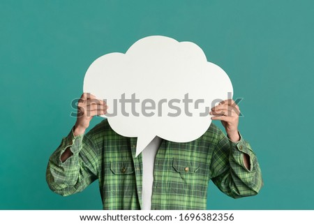 Young guy covering his face with speech bubble on turquoise background, space for design Royalty-Free Stock Photo #1696382356