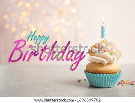 Text Happy Birthday and delicious cupcake with candle on blurred background