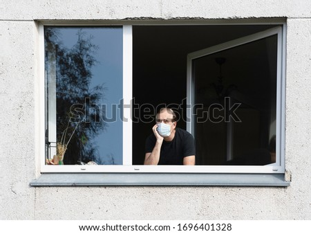 Man in medical protective face mask looking through window.Coronavirus pandemic covid-19.Man in corona quarantine looking out of window to the street.Man with face mask at home.During covid-19 quarant #1696401328