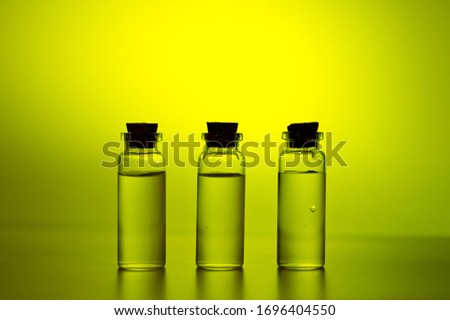 Three glass corked bottles filled with liquid. Background for science and medicine. Virus vaccine. #1696404550