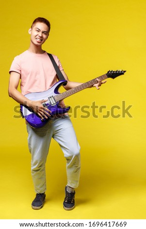 Lifestyle, leisure and youth concept. Vertical portrait of sassy handsome asian man playing electric guitar, smiling pleased, perfoming in band, enjoying jamming, yellow background #1696417669
