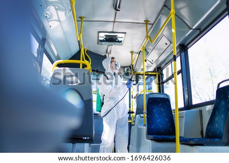 Public transportation healthcare. Man in white protection suit disinfecting and sanitizing handlebars and bus interior to stop spreading highly contagious coronavirus or COVID-19. #1696426036