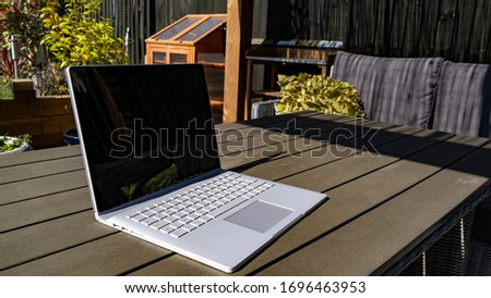 Summer working from home in the garden close up on debranded laptop Royalty-Free Stock Photo #1696463953