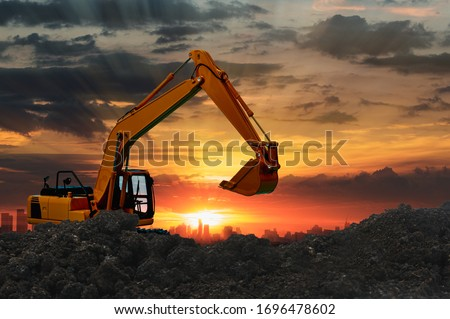 Excavators are digging the soil in the construction site on the  sunset  background #1696478602