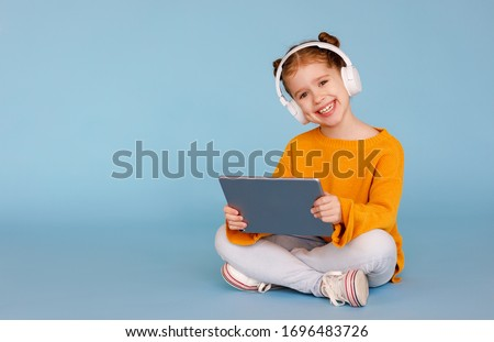 Full length delighted little girl in casual clothes and headphones smiling for camera and listening to music while sitting crossed legged and using tablet on blue background