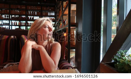 Russian blond woman looking out the window waiting for someone #1696501126