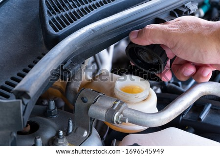 Check brake fluid,Hand open a tank for car maintenance. Royalty-Free Stock Photo #1696545949