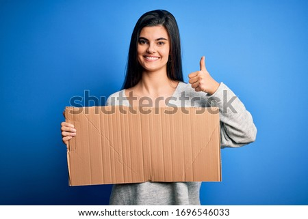 Young beautiful brunette activist woman holding blank cardboard banner protesting happy with big smile doing ok sign, thumb up with fingers, excellent sign
