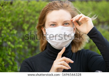 Studio portrait of young woman wearing a face mask, looking at camera, close up, isolated on gray background. Flu epidemic, dust allergy, protection against virus. City air pollution concept #1696566328