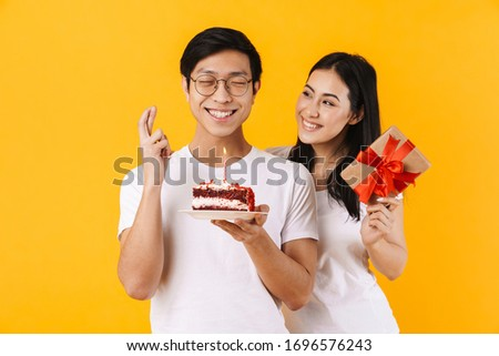 Image of happy multinational couple holding cake and gift box while making wish isolated over yellow background