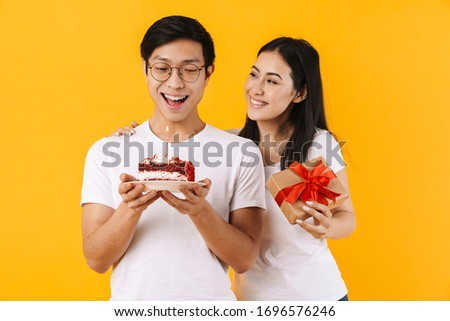 Image of happy multinational couple holding cake and gift box while celebrating birthday isolated over yellow background