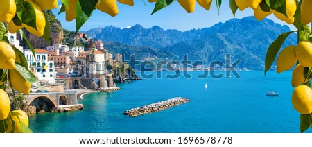 Panoramic view of small town Atrani on Amalfi Coast in province of Salerno, Campania region, Italy. Amalfi coast is popular travel and holyday destination in Italy. Ripe yellow lemons in foreground. Royalty-Free Stock Photo #1696578778