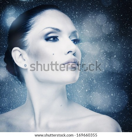 Winter freshness, abstract female portrait with falling snow as background #169660355