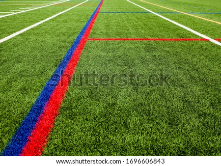 A low angle drone shot of a closed school's football field. It has colorful markings and artificial grass. The picture was taken on a cloudy day, with no people in view. #1696606843