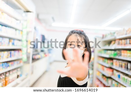Coronavirus Covid-19 concept.Little chinese girl wearing face mask protect from virus and show stop hands gesture for stop corona virus outbreak in supermarket coronavirus and pandemic virus symptoms. #1696614019