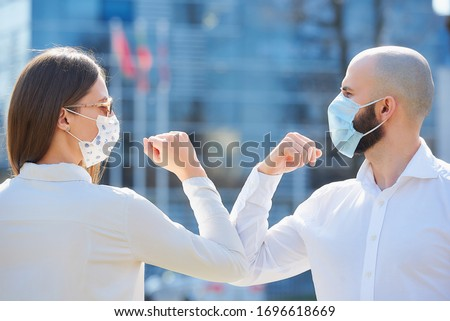 Elbow bumping. Elbow greeting to avoid the spread of coronavirus (COVID-19). Colleagues in shirts meet in the street with bare hands. Instead of greeting with a handshake or a hug, they bump elbows. Royalty-Free Stock Photo #1696618669