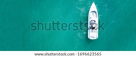 Aerial drone top down ultra wide photo of white speedboat cruise in low speed in emerald clear water lake Royalty-Free Stock Photo #1696623565