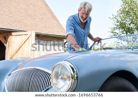 Mature Man Polishing Restored Classic Sports Car Outdoors At Home       Royalty-Free Stock Photo #1696653766
