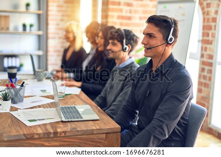 Group of call center workers smiling happy and confident. Working together with smile on face using headset at the office. #1696676281