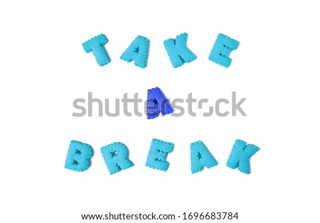 The words TAKE A BREAK spelled with red and blue alphabet shaped biscuits on white background #1696683784
