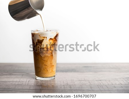 Ice coffee latte with cream being poured into it showing the texture and refreshing look of the drink, with a clean background. #1696700707