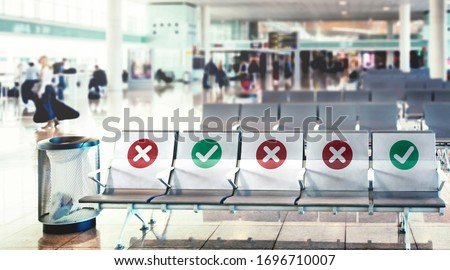 a row of empty chairs with an indication of where it is possible to sit to maintain the social safety distance during the period of the COVID-19 coronavirus pandemic. Social distancing Royalty-Free Stock Photo #1696710007