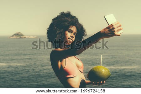 Young dazzling African-American lady is making selfie using her cellphone while standing with a coconut on a resort seashore; charming Brazilian girl is taking pics of herself using the smartphone