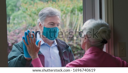 A mature man following the social distancing mandate issued due to COVID19 by not entering the home of his high risk elderly mother that he wants to check on. Royalty-Free Stock Photo #1696740619
