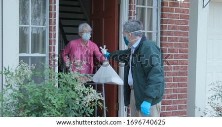 A senior citizen using a walker who is at high risk because of the coronavirus COVID19 gets meals or groceries delivered to her house by a volunteer working with a benevolent organization. Royalty-Free Stock Photo #1696740625
