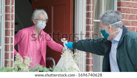 An elderly woman using a walker receives meals from a man working with a benevolent group delivering food to those who are at high risk because of the coronavirus COVID19. Royalty-Free Stock Photo #1696740628
