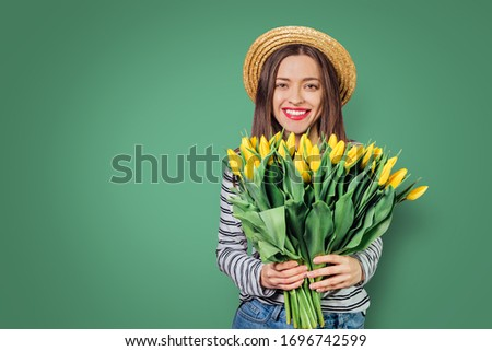 Young woman with tulip flowers on color isolated background #1696742599