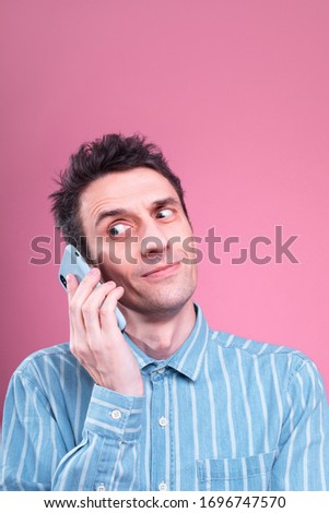 Vertical picture and portrait of young confident man talking on phone. Weird emotions on face. Looking to left. Guy in blue shirt isolated over pink background