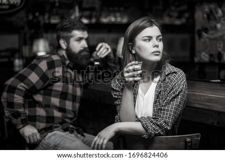 Young woman has problems with alcohol. Female male alcoholism. Woman and man alcoholism. Woman alcoholic beverage in bar. Alcoholism, alcohol addiction, male alcoholic. Black and white. #1696824406