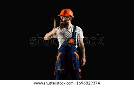 Hammer hammering. Builder in helmet, hammer, handyman, builders in hardhat. Copy space. Bearded builder isolated on black background. Bearded man worker with beard, building helmet, hard hat. #1696829374