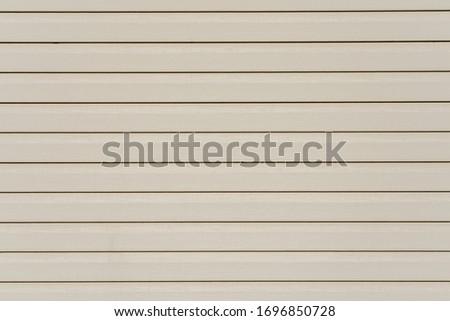 Texture of light beige wooden vinyl siding panel with imitation wood.