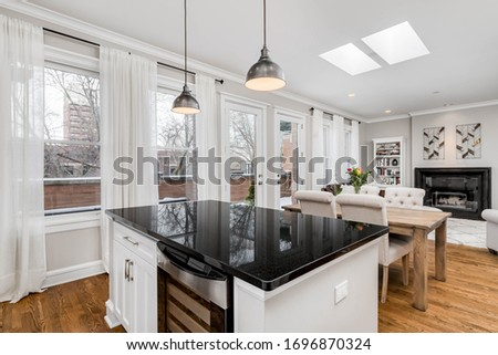 CHICAGO, IL, USA - FEBRUARY 6, 2020: Looking out from a condo kitchen with white cabinets and black granite towards a dining room and living room area. #1696870324