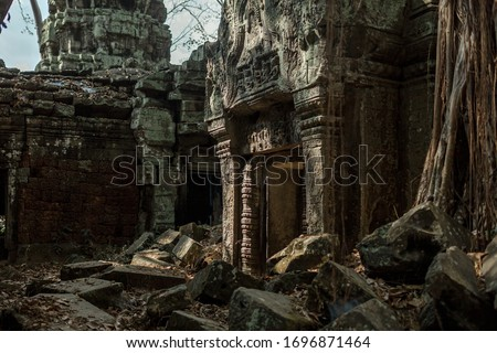 The ruins of the ancient temple of Angkor Wat, Cambodia. Ruined walls. Ancient city overgrown with trees. Royalty-Free Stock Photo #1696871464