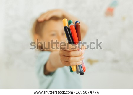 child holds felt-tip pens in hand