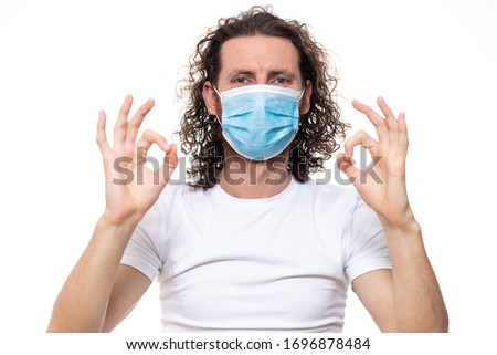 Man in medical mask looks in camera. Man stands in protective medical mask against viruses and infections isolated studio. Pandemic coronavirus epidemic covid-19 #1696878484