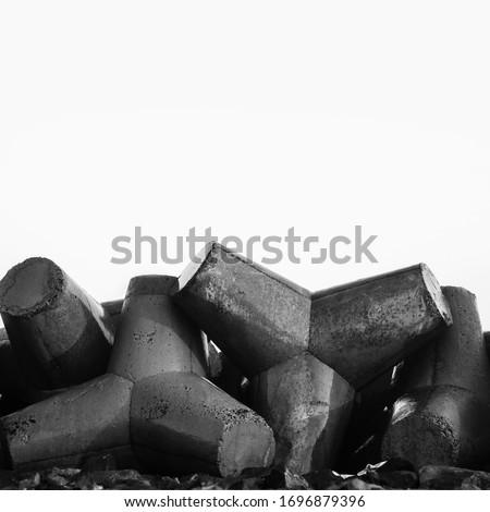 Breakwater concrete tetrapods, wave protection. Coastline, blue sky. Black and white photo. Royalty-Free Stock Photo #1696879396