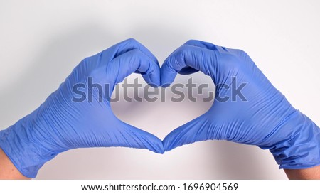 Hands of a doctor or nurse in medical gloves depict a heart on a white background, caring doctor and medicine concept. #1696904569